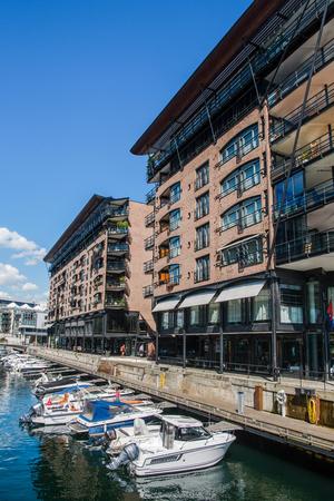 OSLO, NORWAY - 28 JULY, 2018: contemporary houses and boats at shipyard, Aker Brygge district, Oslo Sajtókép