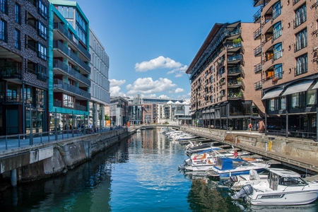 OSLO, NORWAY - 28 JULY, 2018: modern buildings reflected in harbour and moored boats at Aker Brygge district, Oslo Редакционное