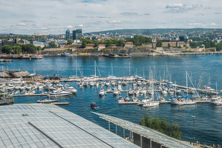 OSLO, NORWAY - 28 JULY, 2018: beautiful city view and boats in harbour at Aker Brygge district, Oslo