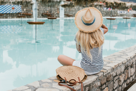 back view of young woman in straw hat sitting near pool in montenegro Stock Photo
