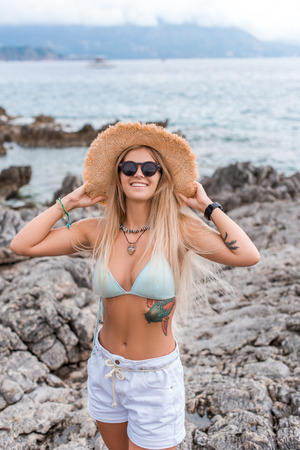 beautiful girl in bikini top touching straw hat at beach in Montenegro Stock Photo