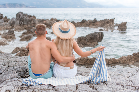 back view of girlfriend and boyfriend sitting on rocky beach in Montenegro