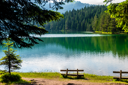 benches on coast of beautiful glacial Black Lake in Montenegro