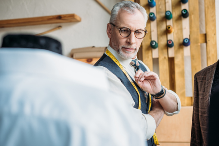 handsome senior tailor looking at jackets on mannequins at sewing workshop Stock Photo