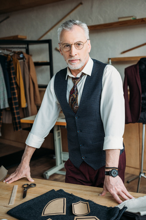 handsome mature tailor standing at workplace in sewing workshop