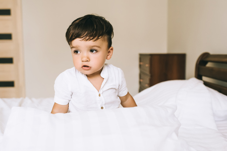 close-up portrait of adorable little child sitting on bed