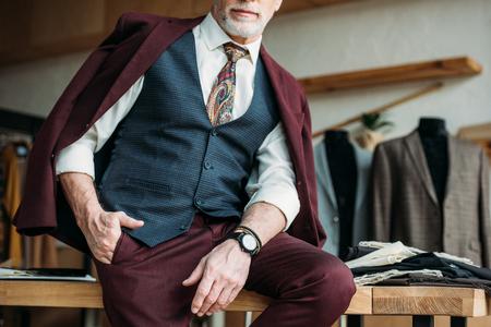 colpo ritagliato di uomo maturo con giacca sulle spalle seduto sul tavolo