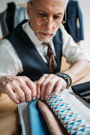 stylish mature tailor looking at cloth samples at sewing workshop Stock Photo