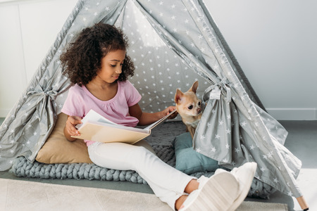 little african american kid reading book with chihuahua dog near by in teepee at home Banque d'images - 109478786