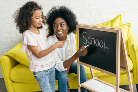 african american woman studying together with daughter at home