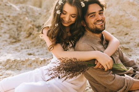 beautiful girl with flowers in hair embracing her happy boyfriend