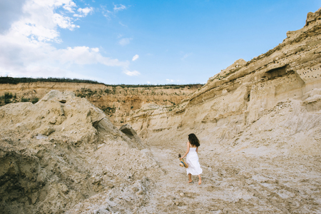 back view of girl in white dress walking in sand canyon with blue sky