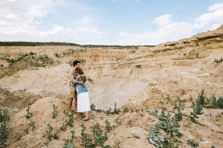 beautiful stylish couple embracing in sand canyon with blue sky