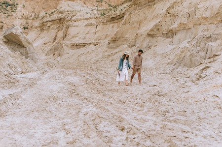 beautiful couple holding hands and walking in sand canyon