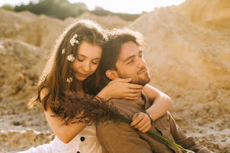 tender attractive girl with flowers in hair embracing her boyfriend and holding floral bouquet in sand canyon