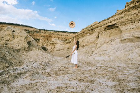 beautiful girl in white dress throwing up straw hat while standing in sand canyon