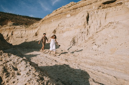 happy couple holding hands and running in sand canyon