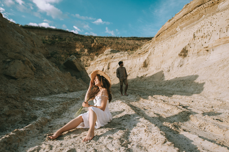 happy girl with floral bouquet sitting in sand canyon with boyfriend behind Banco de Imagens