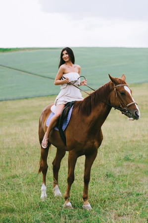 beautiful woman riding brown horse on field