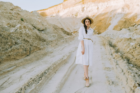 beautiful girl in white dress and straw hat walking in sandy canyon Banco de Imagens