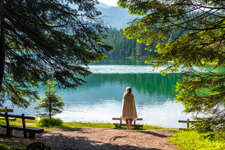 back view of woman in blanket looking at beautiful glacial Black Lake in Montenegro Stockfoto
