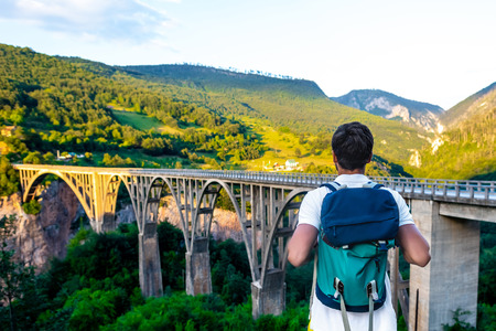 back view of tourist with backpack looking at Tara Bridge in Montenegro