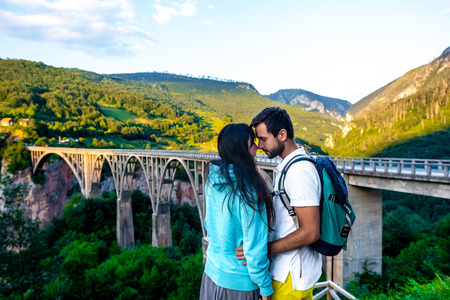couple hugging and touching with foreheads near bridge in Montenegro