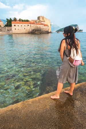 woman standing on pier with Stari Grad (Old Town) on background in Budva, Montenegro