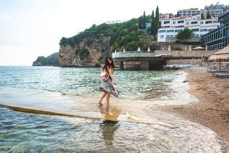 woman walking from pier to ricardova glava beach in Budva, Montenegro Stock Photo