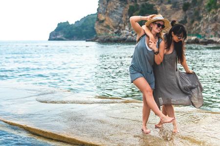 attractive women hugging and having fun on pier at Ricardova Glava beach, Budva, Montenegro