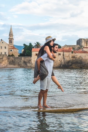 boyfriend giving piggyback to girlfriend on Ricardova Glava beach in Budva, Montenegro