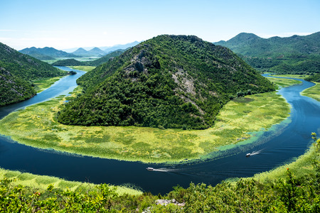 landscape of blue curved Crnojevica River and mountains in Montenegro