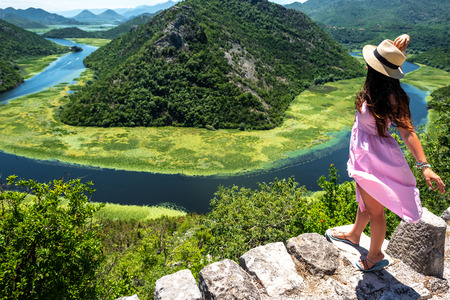high angle view of woman in pink dress and hat standing near Crnojevica River in Montenegro