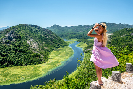 beautiful woman in pink dress standing on stone of viewpoint near Crnojevica River in Montenegro