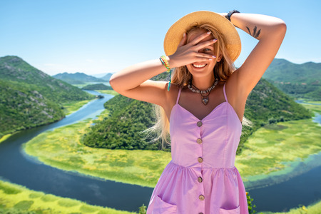 woman in pink dress and hat looking at camera through fingers near Crnojevica River in Montenegro Stock Photo