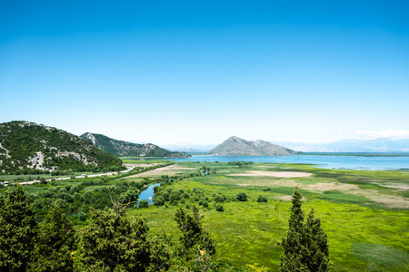 beautiful view of green valley, lake and mountains in Montenegro Stock Photo