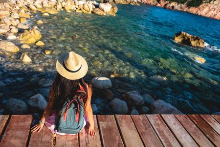 back view of woman sitting on bridge near sea in Budva, Montenegro Stock Photo