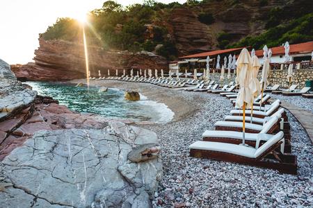 sun loungers on empty beach of adriatic sea with sunlight in Budva, Montenegro