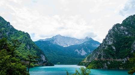 beautiful Piva Lake, mountains and cloudy sky in Montenegro