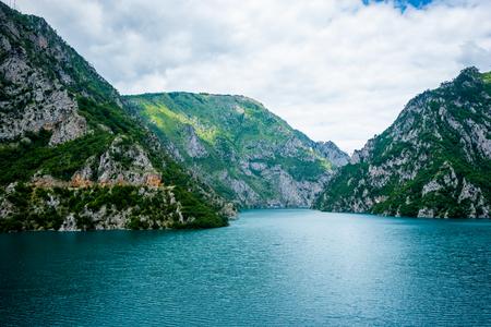 calm blue water of Piva Lake (Pivsko Jezero) and mountains in Montenegro Stock Photo