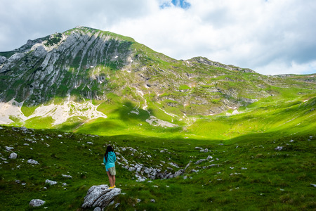 back view of woman standing on stone and looking at mountains in Durmitor massif, Montenegro Stock Photo