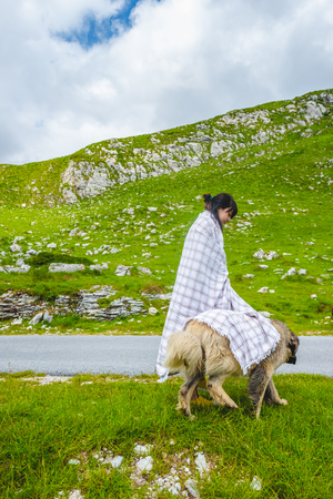 beautiful woman in blanket covering fluffy dog on valley in Durmitor massif, Montenegro