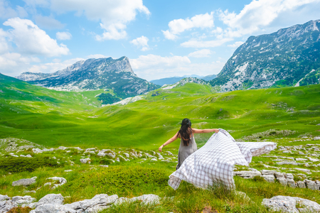 back view of woman running on valley with blanket in Durmitor massif, Montenegro Stock Photo