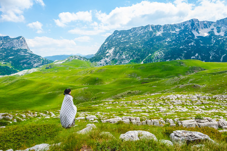 woman in blanket looking at valley in Durmitor massif, Montenegro Stock Photo