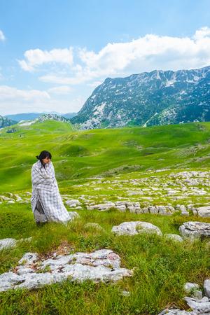 attractive woman in blanket standing on green valley in Durmitor massif, Montenegro Stock Photo