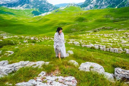 beautiful woman walking in blanket on valley in Durmitor massif, Montenegro Stock Photo