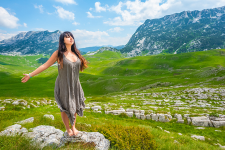 beautiful woman standing with closed eyes and open arms on stone in valley in Durmitor massif, Montenegro