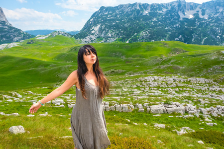 attractive woman standing with closed eyes and open arms on valley in Durmitor massif, Montenegro Stock Photo