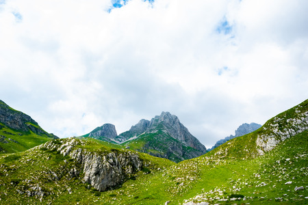 rocky mountains, green grass and cloudy sky in Durmitor massif, Montenegro Stock Photo