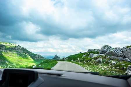 car on mountain road with cloudy sky in Durmitor massif, Montenegro Фото со стока